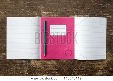 Exercise books and pencil on the wooden background. Copy-space.