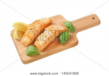 two cooked salmon fillets on wooden cutting board
