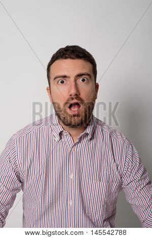 Face expression of an astonished man isolated on gray backgrouns