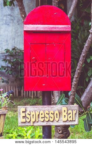 A Old postbox red in garden background.