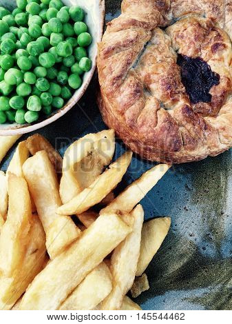 Gourmet steak pie with chunky chips and peas