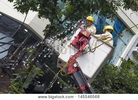 Hanoi, Vietnam - Aug 30, 2016: Asian electrician workers decorating the street with colorful lighting lamps in occasion of big holiday in Hanoi capital city, Vietnam.
