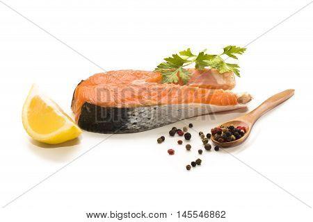 scottish salmon steak with lemon parsley and peppercorn on white background