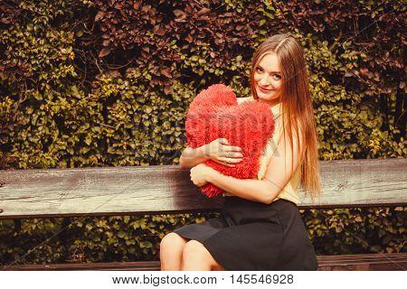 Girl On Bench Holding Heart.