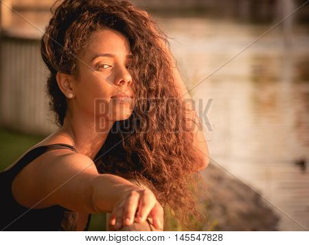 warm portrait of Latina woman with her hair over her face
