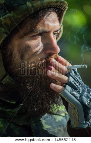 Soldier man with beard on dirty tired face in military camouflage and helmet holding cigarette by hand and smoking outdoor closeup