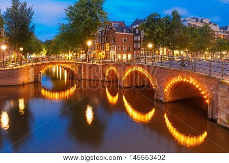 Amsterdam canal, bridge and typical houses, boats and bicycles during evening twilight blue hour, Holland, Netherlands.
