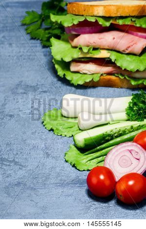 Double sandwich of bread, ham, cheese, tomato, cucumber, onion and lettuce and its ingredients  on spotty blue background. Selective focus