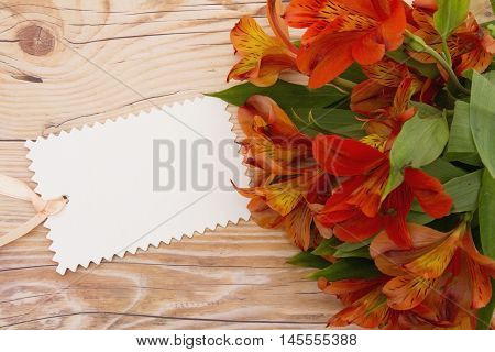 Some lilies on weathered wood with a blank Gift Tag and copy space for your message