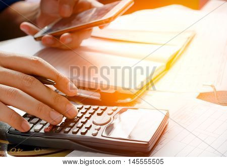 savings finances economy and home concept - close up of man with calculator counting making notes and holding phoneuse mobile phone for searching data in office or home soft focus.