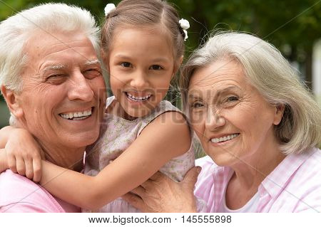 Happy grandparents with granddaughter in summer park