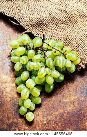 Grapes harvest. White grapes bunch over wooden background. Green grape country rustic style close up with copy space