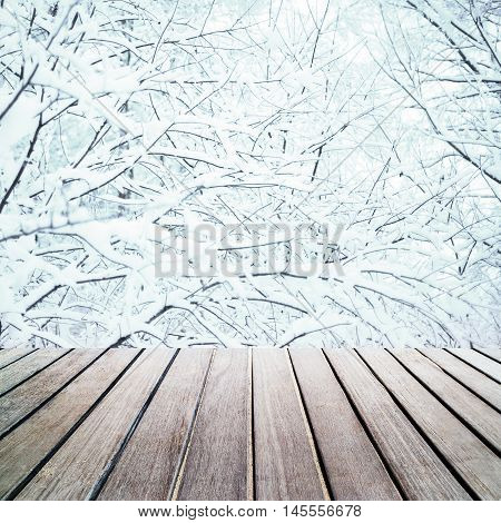 Old vintage brown wood panel tabletop with Abstract Christmas background. Beautiful wood board table in front of Christmas tree branches with white snow. Wall paper ad banner template design