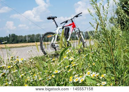 Bicycle on the roadside. Rest during the trip on a bicycle. The beautiful nature around the bicycle. Photo is aimed at promoting a healthy lifestyle.