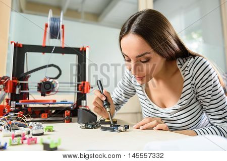 Joyful female engineer is using a voltage and current tester for 3d printer. She is sitting at desk and smiling