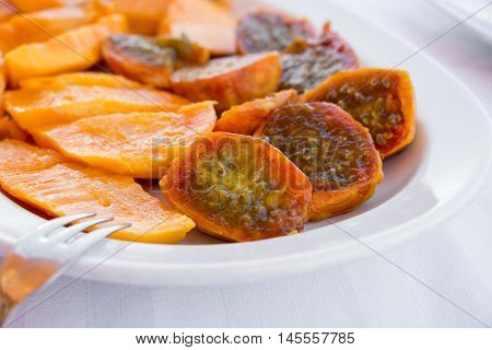 Prickly pear cactus fruits and mango fruits cutted in pieces on the white plate and background. Salad of mango and prickly pear cactus fruits in a white plate. Horizontal. Close.