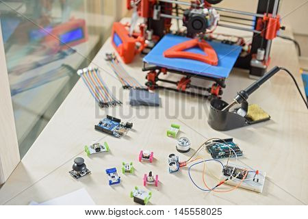 Modern 3d printer with its details on table in office
