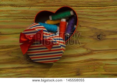 Bobbins of thread in a heart shaped gift box
