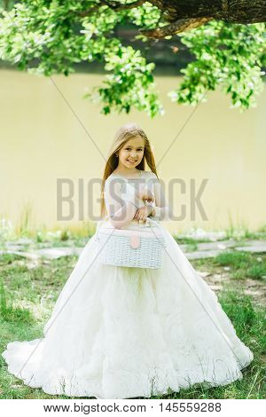 small girl kid with long blonde hair and pretty smiling happy face in prom princess white dress standing sunny day outdoor near water with basket