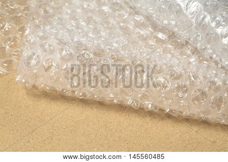 Protective bubble wrap on cardboard texture background. Packaging materials concept, close up.