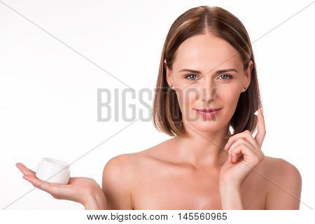 Beauty treatment. Young positive and happy woman holding lotion jar while taking care of her dry complexion applying moisturizing cream being on isolated white background