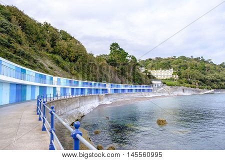 Lovely seaside scene at Meadfoot Bay Torquay in Devon England with its colorful blue beach huts sheltered by trees