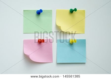 Group of colorful note papers and thumbtack with white background.