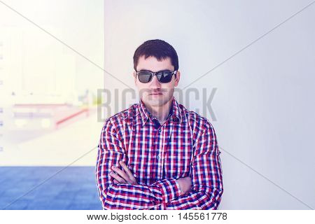 The man in the summer against the wall, glasses, serious Chief Executive Officer, in jeans and a shirt, a bright sunny day. The idea of the concept of a businessman in the city. Lifestyle, portrait of a successful man close up.