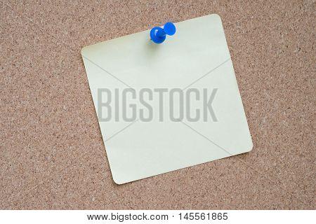 Yellow sticker pinned blue pushpin with cork background.