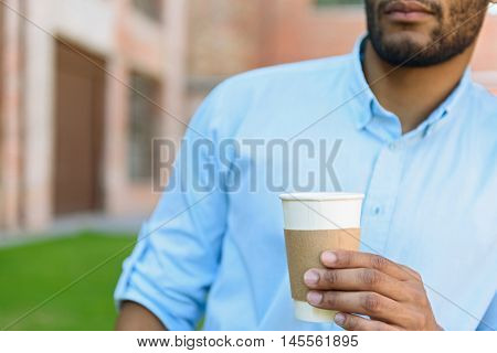 Dreamful young man is enjoying hot coffee outdoors. Focus on cup