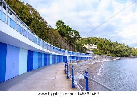 Beautiful row of colorful blue beach huts by the sea at Meadfoot Bay in the English Riviera town of Torquay Devon England