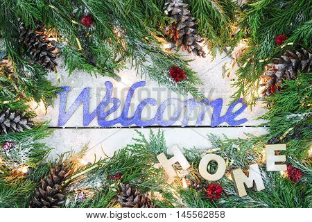 Holiday welcome Home sign  with green Christmas tree garland border, snow and lights on antique rustic wooden background