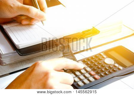 close up of man with calculator counting making notes at home hand is writes in a notebook with books soft focus.