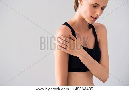Complain. Cropped image of sad young woman having shoulders ache being on isolated grey background