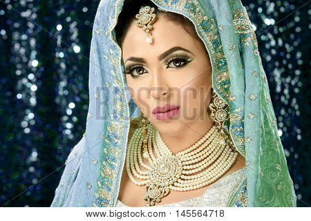 Portrait of a pretty girl dressed as traditional indian pakistani bride with heavy makeup and jewellery