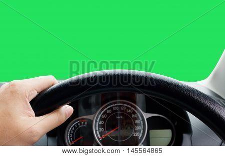 Man's hands of a driver on steering wheel of a minivan car on asphalt roadInside car dashboard is green.