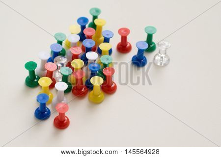 Closeup of colorful pushpin on cream background.