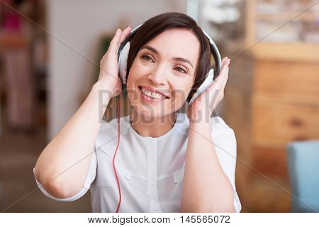 Influence of music. Portrait of happy and smiling young woman listening music using headphones