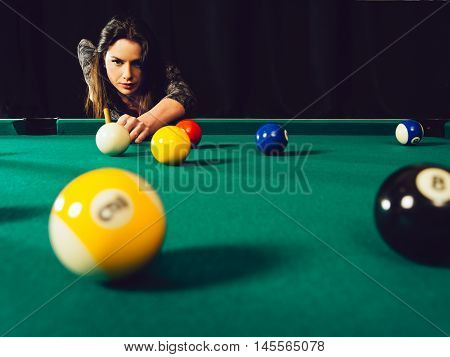 Photo of a beautiful woman leaning over a pool table playing pool.