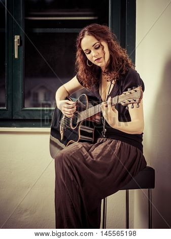 Photo of a beautiful brunette female playing an acoustic guitar by the window.