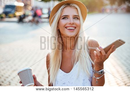 Close up portrait of a girl in hat holding take away coffee cup and smartphone