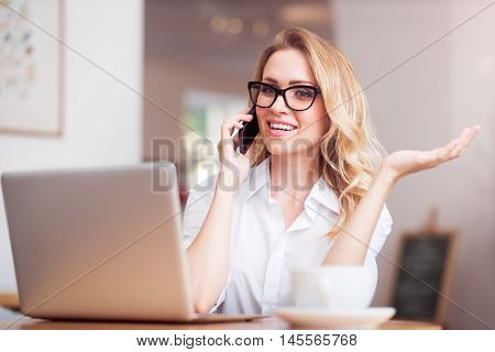 Idle talker. Smiling and merry young woman talking per smart phone and using laptop while working and sitting at the table