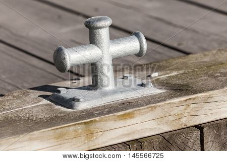 Small Gray Mooring Bollard On Wooden Pier