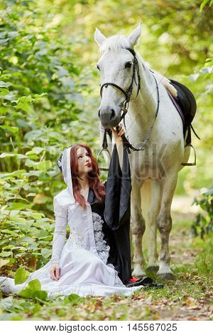 Young woman in black and white dress sits near horse in park.