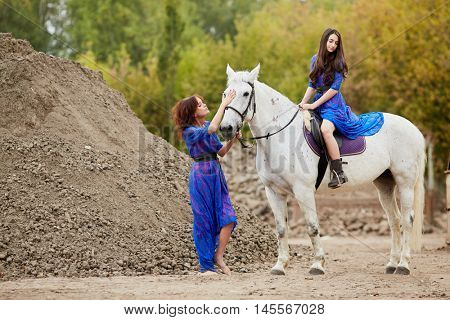 Woman holds by bridle white horse on which her daughter sits in park near ground pile.