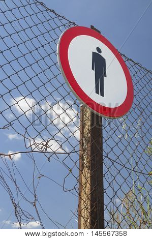 No entry sign on a incomplete net fence blue sky in the background
