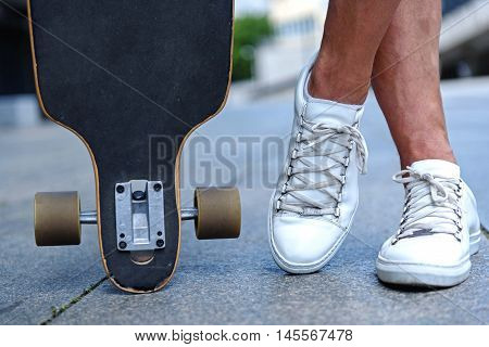 Close up of male feet resting after skateboarding. Man is standing near skate with relaxation