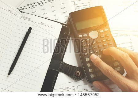 savings finances economy and office concept - close up of man with calculator counting making notes pen on the note book and bill at desk office data analysis soft focus.