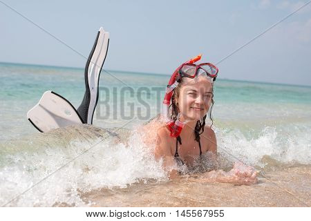 Girl in the sea wearing a flippers and mask for diving