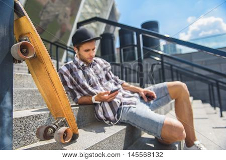 Pensive young man is sitting on steps near skateboard. He is using mobile phone while wearing headphones. Focus on skate